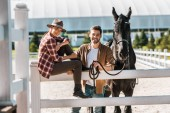 Fotografie smiling female equestrian sitting on fence, colleague standing near fence with horse at ranch
