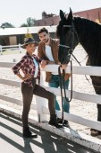 female and male equestrians standing near fence with horse at ranch and looking at camera