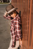 attractive woman in checkered shirt touching hat, leaning on brown wall at ranch and looking at camera