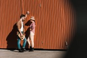 man and woman in casual clothes leaning on brown wall and looking at each other at ranch