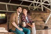 usmívající se muž a žena sedí s jednorázovými skleničky na ranči