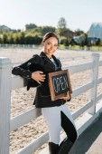 Fotografie attractive female equestrian leaning on fence and holding open sign at horse club