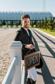Fotografie handsome smiling equestrian leaning on fence, holding open sign and looking at camera at ranch