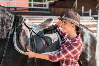 side view of smiling attractive female equestrian fixing horse saddle at ranch