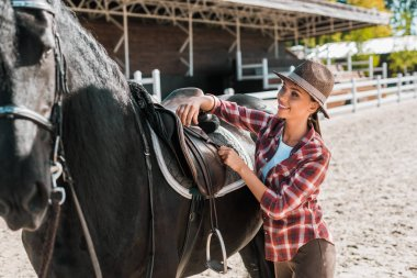 attractive cowgirl in checkered shirt fixing horse saddle at ranch