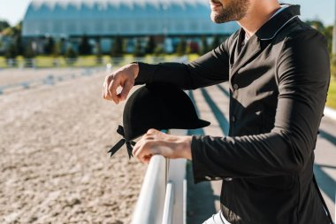 cropped image of male equestrian leaning on fence with riding helmet at horse club