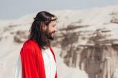 boční pohled na usmívající se Ježíš v roucho, červenou šerpou a korunu z trní koukal v poušti