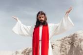 Fotografie nízký úhel pohled na Ježíše v roucho, červenou šerpou a korunu z trní s zvedl ruce v poušti