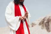 Fotografie cropped image Jesus holding wooden rosary and praying in desert