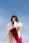 Fotografie low angle view of Jesus Christ in robe, red sash and crown of thorns holding rosary and praying against blue sky