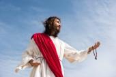 nízký úhel pohled na Ježíše v šat drží růženec a dosažení ruku proti modré obloze