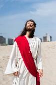 Fotografia Gesù in vestaglia, fascia rossa e corona di spine in piedi sulla sabbia con gli occhi chiusi, edifici su priorità bassa