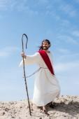 Fotografie usmívající se Ježíš v roucho, červenou šerpou a korunu z trní stojící s dřevěnými zaměstnanci v poušti