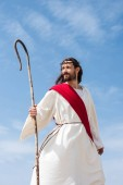 Fotografie cheerful Jesus in robe, red sash and crown of thorns standing with wooden staff in desert