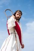 Fotografie nízký úhel pohled na Ježíše v roucho, červenou šerpou a trnová koruna stojí s dřevěnými zaměstnanci v poušti a při pohledu na fotoaparát
