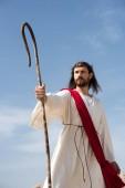 Fotografie Ježíš v roucho, červenou šerpou a korunu z trní stojící s dřevěnými zaměstnanci v poušti