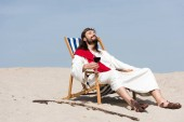 Photo Jesus in robe and red sash resting on sun lounger with glass of red wine in desert