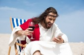 Photo angry Jesus resting on sun lounger with glass of wine and screaming at smartphone in desert