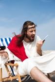 Fotografie Angry Jesus auf Sonnenliege mit Glas Wein sitzen und schreiend auf Smartphone in Wüste