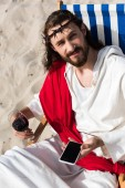Fotografie Jesus resting on sun lounger with glass of wine and holding smartphone with blank screen in desert
