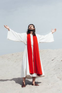 Jesus in robe, red sash and crown of thorns standing with raised hands and talking with god in desert stock vector
