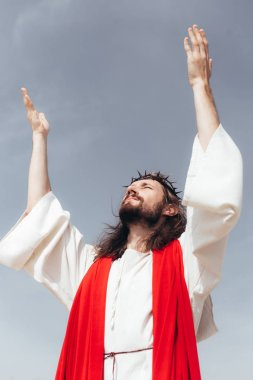 Low angle view of Jesus in robe, red sash and crown of thorns standing with raised hands against grey sky stock vector