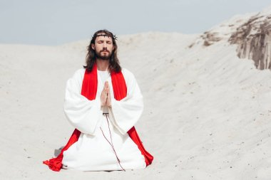 Jesus with closed eyes standing on knees on sand and praying in desert