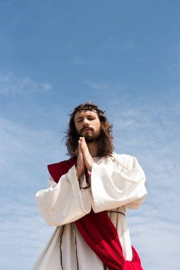 low angle view of Jesus in robe, red sash and crown of thorns holding rosary and praying with closed eyes against blue sky
