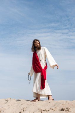 Elbise, kırmızı kuşak ve tespih tutan ve çölde kum tepe üzerinde yürüme dikenli taç İsa