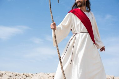 cropped image of smiling Jesus in robe and red sash standing with wooden staff in desert