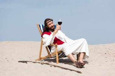 Jesus in robe and red sash resting on sun lounger and looking at glass of red wine in desert