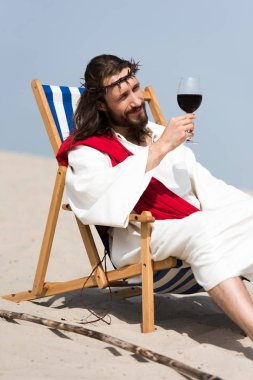 cheerful Jesus in robe and red sash resting on sun lounger and looking at glass of red wine in desert