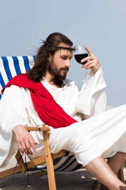 pensive Jesus in robe and red sash sitting on sun lounger with glass of red wine in desert