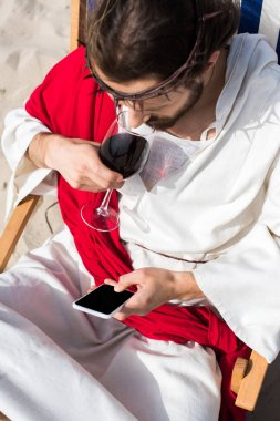 high angle view of Jesus resting on sun lounger, drinking wine and using smartphone with blank screen in desert