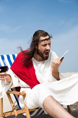 angry Jesus sitting on sun lounger with glass of wine and screaming at smartphone in desert
