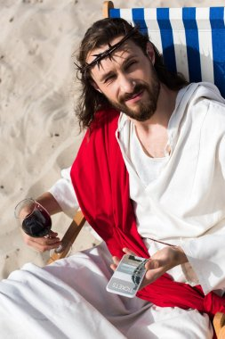 Jesus resting on sun lounger with glass of wine and holding smartphone with tickets website in desert