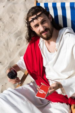 Jesus resting on sun lounger with glass of wine and holding smartphone with youtube page in desert