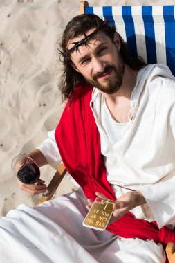 Jesus resting on sun lounger with glass of wine and holding smartphone with medical appliance in desert