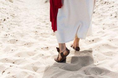 bornoz, sandalet ve kırmızı kuşak çölde kum üzerinde yürüyen İsa'nın resim kırpılmış