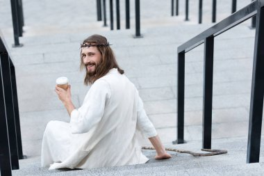 Back view of smiling Jesus in robe and crown of thorns sitting on stairs and holding disposable coffee cup on street stock vector