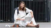 Fotografie cheerful Jesus in robe and crown of thorns sitting on skateboard and using laptop in city