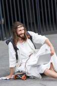 Fotografie usmívající se Ježíš v roucho a korunu z trní na skateboard s notebookem a koukal v městě