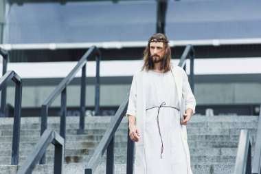 Jesus in robe and crown of thorns walking on stairs with laptop and listening music in city