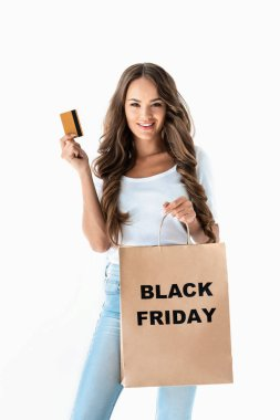 Beautiful young woman holding golden credit card and shopping bag with black friday sign, isolated on white stock vector