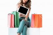 Ausgeschnittene Ansicht eines Mädchens mit Einkaufstaschen, die ein digitales Tablet mit leerem Bildschirm zeigen, isoliert auf weiß
