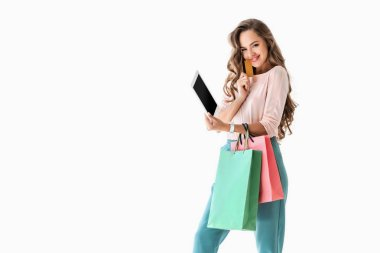 young smiling woman with shopping bags shopping online with tablet and credit card, isolated on white