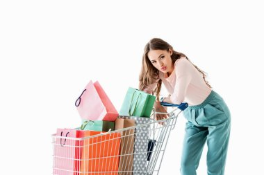 attractive tired girl with shopping cart and bags, isolated on white