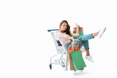 happy beautiful girl sitting in shopping cart with bags, isolated on white