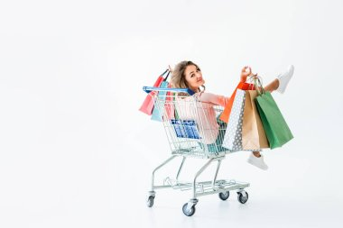 beautiful happy girl with shopping bags sitting in shopping cart, isolated on white