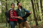 Photo man and woman looking for destination on map while hiking in forest together